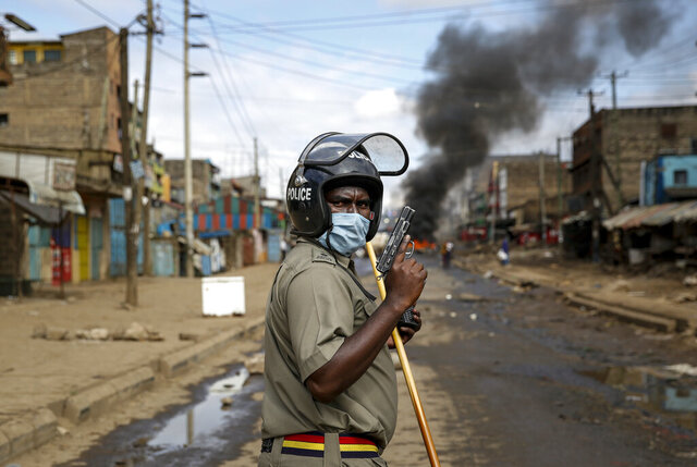 A police officer holds a pistol during clashes with protesters near a burning tyre barricade in the Kariobangi slum of Nairobi, Kenya Friday, May 8, 2020. Hundreds of protesters blocked one of the capital's major highways with burning tires to protest government demolitions of the homes of more than 7,000 people and the closure of a major food market, causing many to sleep out in the rain and cold because of restrictions on movement due to the coronavirus. (AP Photo/Brian Inganga)