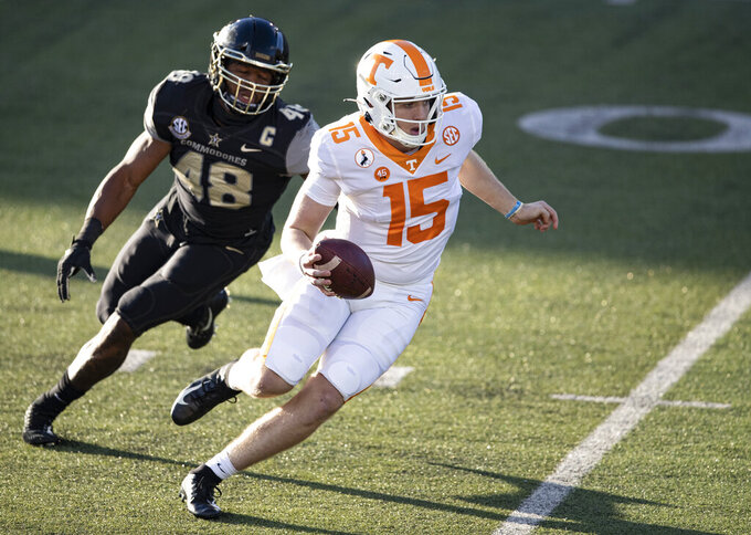 Tennessee quarterback Harrison Bailey (15) runs for yardage as he is chased by Vanderbilt linebacker Andre Mintze (48) during the first half of an NCAA college football game Saturday, Dec. 12, 2020, in Nashville, Tenn. (AP Photo/Wade Payne)