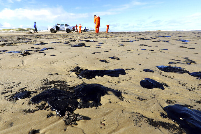 CORRECTS DATE - In this Oct. 7, 2019 handout photo released by the Aracaju Municipal Press Office, workers remove oil from Viral Beach, in Aracaju, Brazil. The oil that has been polluting Brazil's northeastern beaches since early September is likely coming from Venezuela, according to a report by Brazil's state oil company cited by the country's environment minister. The oil sludge has now reached 61 municipalities in nine Brazilian states, contaminating over 130 beaches, in what Brazilian officials have called an