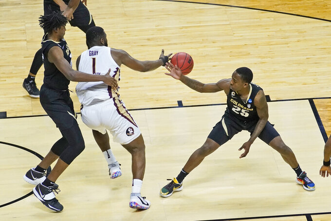 Colorado guard McKinley Wright IV (25) steals the ball from Florida State forward RaiQuan Gray (1) during the second half of a second-round game in the NCAA college basketball tournament at Farmers Coliseum in Indianapolis, Monday, March 22, 2021. (AP Photo/Charles Rex Arbogast)