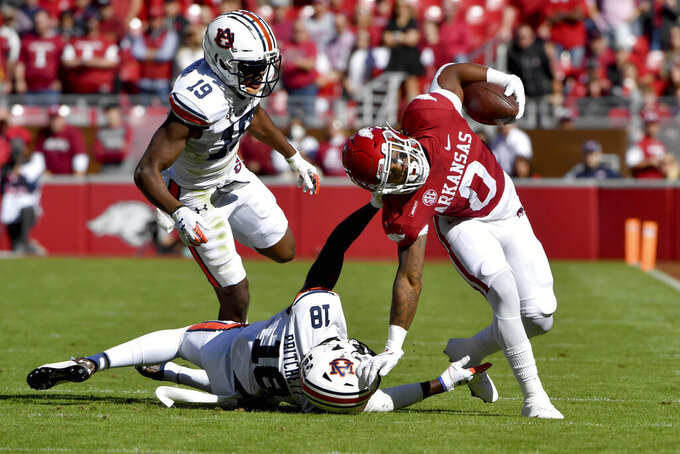 Arkansas running back AJ Green (0) is taken down by Auburn defenders Nehemiah Pritchett (18) and Bydarrius Knighten (19) during the first half of an NCAA college football game Saturday, Oct. 16, 2021, in Fayetteville, Ark. (AP Photo/Michael Woods)