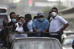 Commuters, wearing protective face masks, travel in the bed of a truck as public transportation has been temporarily suspended by the government in an effort to contain the spread of the new coronavirus, in San Salvador, El Salvador, Friday, Aug. 7, 2020. For months, the strictest measures confronting the COVID-19 pandemic in Latin America seemed to keep infections in check in El Salvador, but a gradual reopening combined with a political stalemate has seen infections increase nearly fourfold. (AP Photo/Salvador Melendez)