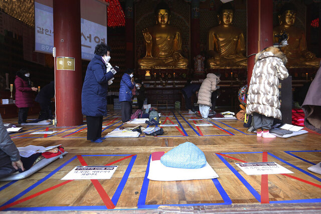 Social distancing signs are seen on the floor as parents pray during a special service to wish for their children's success in the upcoming college entrance exam on Thursday, Dec. 3, at the Jogye Temple in Seoul, South Korea, Sunday, Nov. 29, 2020. South Korea is shutting down indoor gyms offering intense workout classes and banning year-end parties at hotels in the greater Seoul area to fight the virus. Prime Minister Chung Sye-kyun said Sunday. The signs read: