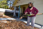 In this Friday, Nov. 22, 2019, photo, Elizabeth Watling spreads leaves over her garden to prepare it for winter while wearing a mask to protect against dust in Chico, Calif. Watling says her throat has been easily irritated since she was exposed to the huge smoke plume from a wildfire that destroyed the nearby town of Paradise the year before, killing 85 people and destroying more than 14,000 homes. (AP Photo/Matthew Brown)
