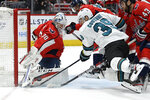 Washington Capitals goaltender Braden Holtby (70) and San Jose Sharks center Logan Couture (39) battle for the puck during the first period of an NHL hockey game, Sunday, Jan. 5, 2020, in Washington. (AP Photo/Nick Wass)