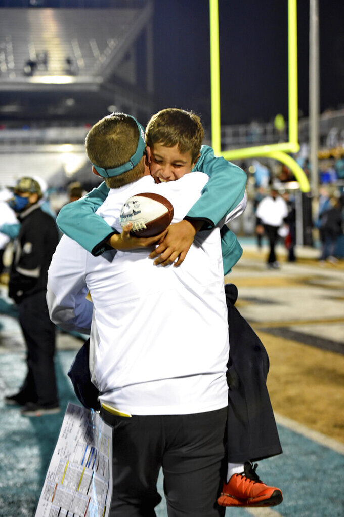 Coastal Carolina head coach Jamey Chadwell, back, hugs his son Jameson after an NCAA college football game against BYU, Saturday, Dec. 5, 2020, in Conway, S.C. (AP Photo/Richard Shiro)