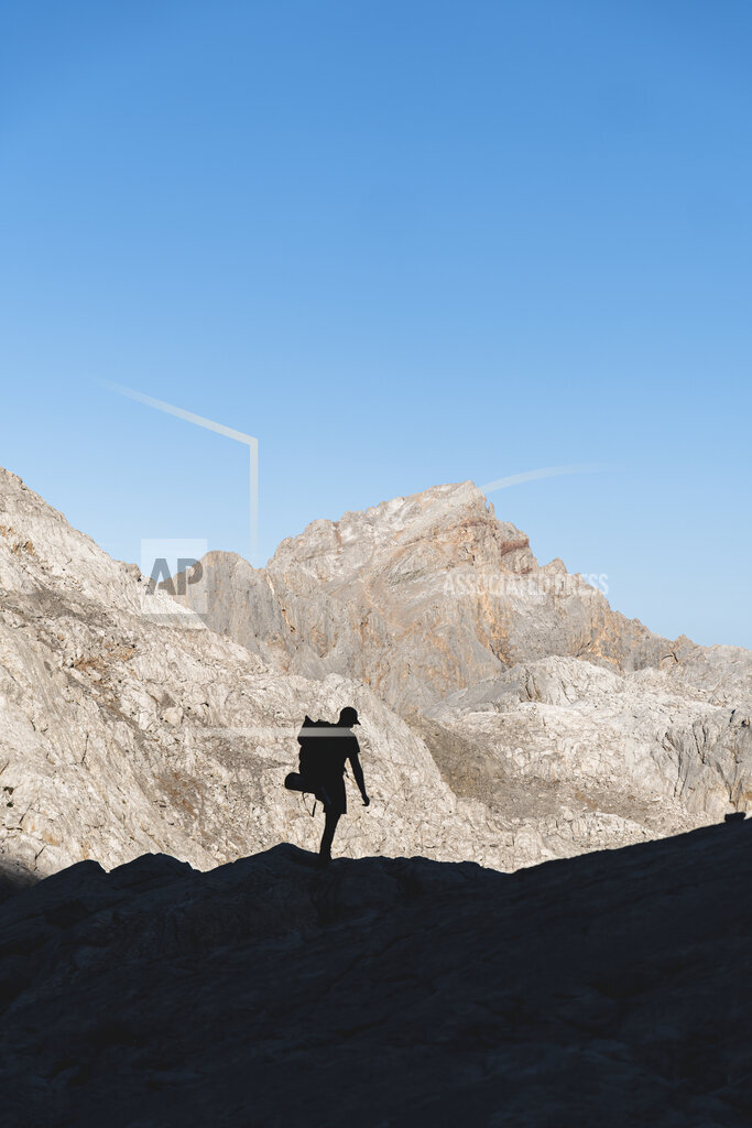 Male tourist hiking on Picos de Europe mountain range during vacation, Cantabria, Spain