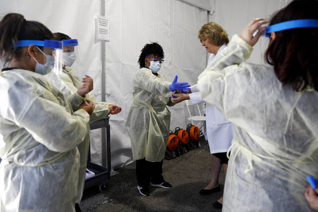 Doctors and healthcare workers with the University of Nevada, Las Vegas School of Medicine suit up in personal protective equipment before taking patients at a drive-thru coronavirus testing site Tuesday, March 24, 2020, in Las Vegas. UNLV Medicine, the clinical arm of the UNLV School of Medicine, started conducting COVID-19 testing by appointment for people who meet the Centers for Disease Control and Prevention guidelines. (AP Photo/John Locher)