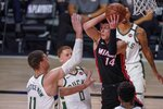Miami Heat's Tyler Herro looks to pass past Milwaukee Bucks' Brook Lopez (11) and Donte DiVincenzo during the first half of an NBA conference semifinal playoff basketball game Sunday, Sept. 6, 2020, in Lake Buena Vista, Fla. (AP Photo/Mark J. Terrill)