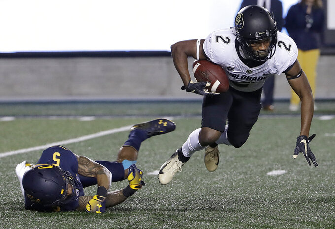 Colorado's Ronnie Blackmon, right, runs past California's Trey Turner III while returning a kick during the second half of an NCAA college football game in Berkeley, Calif., Saturday, Nov. 24, 2018. California won, 33-21. (AP Photo/Jeff Chiu)