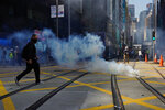 A protester approaches a gas canister deployed in Central district of Hong Kong on Monday, Nov. 11, 2019. A protester was shot by police Monday in a dramatic scene caught on video as demonstrators blocked train lines and roads during the morning commute. (AP Photo/Vincent Yu)