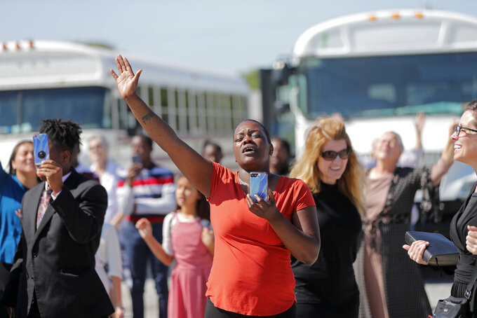 FILE - In this April 21, 2020, file photo, members of the Life Tabernacle Church sing spiritual songs and hold their hands in the air as they wait for pastor Tony Spell to leave the East Baton Rouge Parish jail in Baton Rouge, La. Louisiana authorities arrested the pastor on an assault charge after he admitted that he drove his church bus toward a man who has been protesting his decision to hold mass gatherings in defiance of public health orders during the coronavirus pandemic. (AP Photo/Gerald Herbert, File)