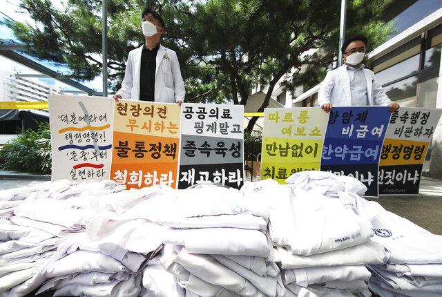 Doctors hold signs criticizing the government's medical policy at a hospital in Suwon, South Korea, Wednesday, Aug. 26, 2020. Health officials in South Korea called on thousands of striking doctors to return to work as the country counted its 13th straight day of triple-digit daily jumps in coronavirus cases. The sign reads: