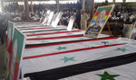 FILE - In this Thursday, July 26, 2018, file photo, released by the Syrian official news agency SANA, mourners attend a mass funeral of people killed a day earlier by a series of suicide bombings launched by the Islamic State's fighters on the eastern and northern countryside of the southern province of Sweida, Syria. Syrian troops have liberated 19 women and children hostages held by the Islamic State group since July in a military operation in the country's center, ending a crisis that has stunned Syria's Druze minority, state media reported Thursday, Nov. 8, 2018. (SANA via AP, File)