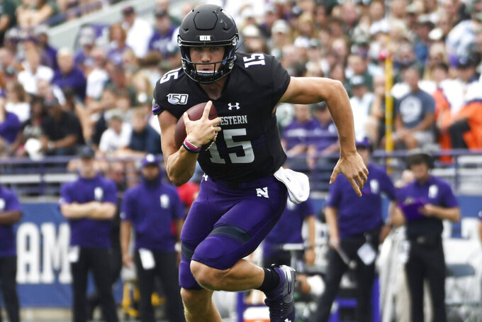 Northwestern quarterback Hunter Johnson (15) runs the against Michigan State during the first half of an NCAA college football game, Saturday, Sept. 21, 2019, in Evanston, Ill. (AP Photo/David Banks)