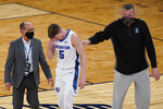 Creighton coach Greg McDermott, right, and a trainer check on Alex O'Connell (5) after O'Connell was hurt during the first half of the team's NCAA college basketball game against Butler in the Big East men's tournament Thursday, March 11, 2021, in New York. (AP Photo/Frank Franklin II)