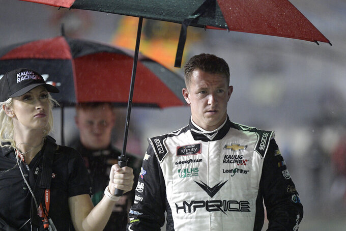 AJ Allmendinger, right, leaves pit road during a rain delay in a NASCAR Xfinity Series auto race at Daytona International Speedway, Friday, Aug. 27, 2021, in Daytona Beach, Fla. (AP Photo/Phelan M. Ebenhack)