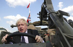 FILE - In this Thursday, June 21, 2018 file photo Britain's Foreign Secretary Boris Johnson talks to a British armed forces serviceman based in Orzysz, in northeastern Poland, during a ceremony at the Tomb of the Unknown Soldier and following talks on security with his Polish counterpart Jacek Czaputowicz in Warsaw, Poland. (AP Photo/Czarek Sokolowski, File)