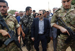 Lebanese Foreign Minister Gibran Bassil, center, escorted by the Lebanese army, visits a Syrian refugee camp, in Arsal, near the border with Syria, east Lebanon, Wednesday, June 13, 2018. A public spat between the Lebanese government and the United Nation's refugee agency deepened Wednesday as Lebanon's caretaker foreign minister kept up his criticism, accusing the agency of discouraging Syrian refugees from returning home. Lebanon is home to more than a million Syrian refugees, or about a quarter of the country's population, putting a huge strain on the economy. (AP Photo/Hussein Malla)