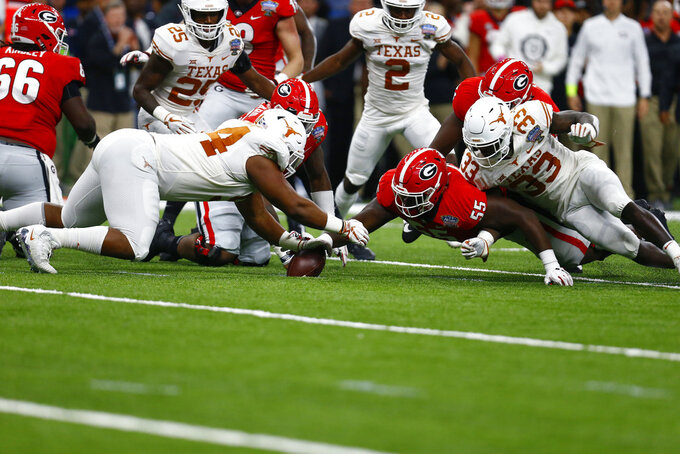 Texas defensive lineman Gerald Wilbon (94) recovers a fumble by Georgia as Georgia offensive lineman Trey Hill (55) reaches for the ball during the first half of the Sugar Bowl NCAA college football game in New Orleans, Tuesday, Jan. 1, 2019. (AP Photo/Butch Dill)