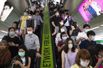 FILE - In this Feb. 7, 2020, file photo, commuters wear face masks to protect themselves from new virus at the skytrain station in Bangkok, Thailand. The virus outbreak that began in China and has spread to more than 20 countries is stretching already-strained public health systems in Asia and beyond, raising questions over whether everyone can get equal access to treatment. (AP Photo/Sakchai Lalit, File)