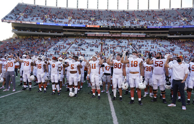 "Texas players, including Sam Ehlinger (11), sing ""The Eyes Of Texas"" after an NCAA college football game against Baylor in Austin, Texas, Saturday, Oct. 24, 2020. (AP Photo/Chuck Burton)"