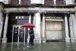 A man walks past a closed cafe in a flooded Venice, Italy, Tuesday, Nov. 12, 2019. The high tide reached a peak of 127cm (4.1ft) at 10:35am while an even higher level of 140cm(4.6ft) was predicted for later Tuesday evening. (AP Photo/Luca Bruno)