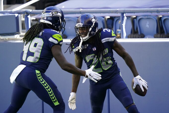 FILE - In this Sept. 27, 2020, file photo, Seattle Seahawks cornerback Shaquill Griffin (26) is greeted by his twin brother, outside linebacker Shaquem Griffin (49), after Shaquill Griffin intercepted a Dallas Cowboys pass during the first half of an NFL football game in Seattle. Shaquill Griffin is returning to the Sunshine State. He could be bringing his twin brother with him. A person familiar with negotiations says Griffin and the Jacksonville Jaguars agreed on a three-year contract worth up to $44.5 million that includes $29 million guaranteed. (AP Photo/Elaine Thompson, File)