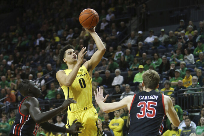 Oregon's Will Richardson, center, shoots between Utah's Both Gach, left, and Branden Carlson during the first half of an NCAA college basketball game in Eugene, Ore., Sunday, Feb. 16, 2020. (AP Photo/Chris Pietsch)