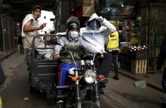 """Men wearing face masks ride a motorcycle that hauls a trailer in the """"Villa 31"""" neighborhood during a government-ordered lockdown to curb the spread of the new coronavirus in Buenos Aires, Argentina, Tuesday, May 5, 2020. According to official data, the number of confirmed cases of COVID-19 disease in this city's slum have increased in the past week, putting authorities on high alert. (AP Photo/Natacha Pisarenko)"""