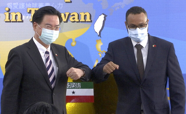 Taiwan's Foreign Minister Joseph Wu, left, and Somaliland representative to Taiwan, Mohamed Hagi, bump elbows during an unveiling ceremony of the Somaliland office plate in Taipei, on Wednesday, Sept. 9, 2020. The breakaway territory of Somaliland opened a representative office in Taipei on Wednesday in a move that has already drawn Beijing's ire.(AP Photo/Johnson Lai)