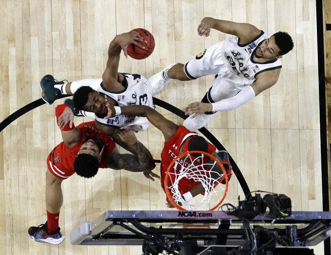 Michigan State's Xavier Tillman (23) drives against Texas Tech's Brandone Francis and Tariq Owens (11) as Michigan State's Kenny Goins (25) watches during the first half in the semifinals of the Final Four NCAA college basketball tournament, Saturday, April 6, 2019, in Minneapolis. (AP Photo/David J. Phillip)