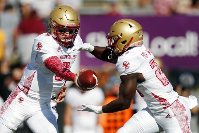 Boston College quarterback Phil Jurkovec (5) passes off to running back Alec Sinkfield (26) during the first half of an NCAA college football game against Massachusetts, Saturday, Sept. 11, 2021, in Amherst, Mass. (AP Photo/Michael Dwyer)