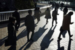 Commuters wearing face mask make their way during a rush hour Friday, Jan. 8, 2021 in Tokyo. Japanese Prime Minister Yoshihide Suga declared a state of emergency Thursday for Tokyo and three other prefectures to ramp up defenses against the spread of the coronavirus. (AP Photo/Eugene Hoshiko)