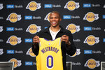 Los Angeles Lakers guard Russell Westbrook poses for a photo with his jersey at an introductory NBA basketball news conference in Los Angeles, Tuesday, Aug. 10, 2021. (AP Photo/Kyusung Gong)