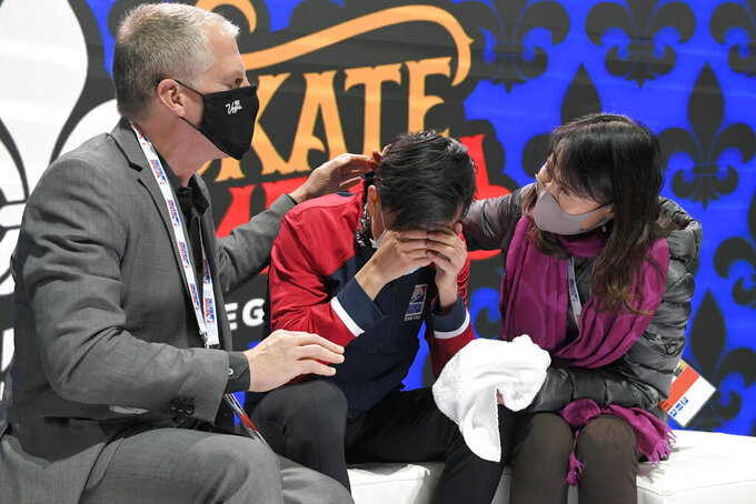 Vincent Zhou, center, reacts after receiving his final scores in the mens free skate at the Skate American figure skaint event Saturday, Oct. 23, 2021, in Las Vegas. (AP Photo/David Becker)