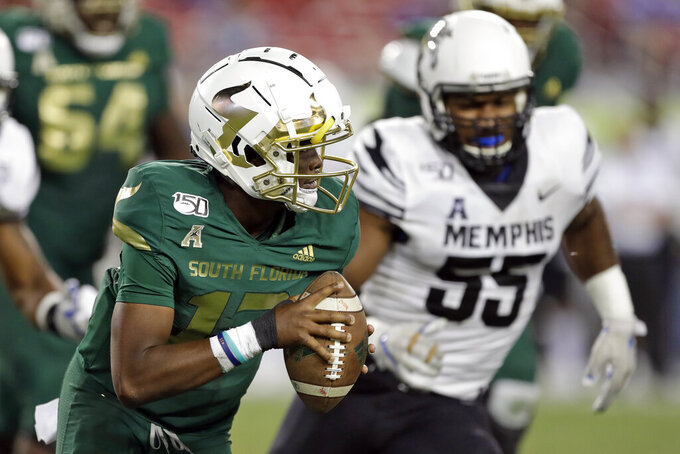 South Florida quarterback Jordan McCloud (12) scrambles away from Memphis defensive end Bryce Huff (55) during the second half of an NCAA college football game Saturday, Nov. 23, 2019, in Tampa, Fla. (AP Photo/Chris O'Meara)