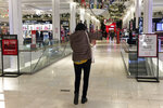 A shopper walks through Macy's flagship store at Herald Square an hour after its 6a.m. Black Friday opening, Friday, Nov. 27, 2020, in New York. (AP Photo/Anne D'Innocenzio)