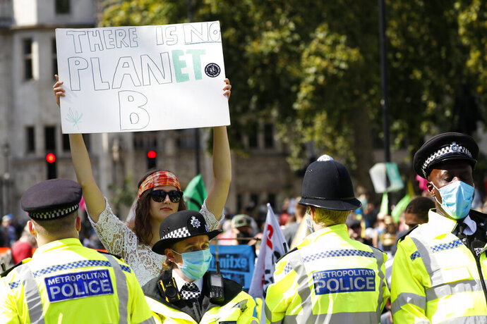 A demonstrator holds up a poster at Parliament Square during an Extinction Rebellion climate change protest in London, Tuesday, Sept 1, 2020. (AP Photo/Alastair Grant)
