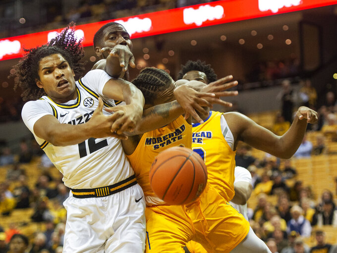 Missouri's Dru Smith, left, and Jeremiah Tilmon, top, battle Morehead State's Justin Thomas for a rebound during the first half of an NCAA college basketball game Wednesday, Nov. 20, 2019, in Columbia, Mo. (AP Photo/L.G. Patterson)