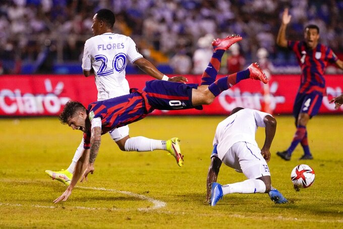 United States' Christian Pulisic, left, jumps over Honduras' Maynor Figueroa during a qualifying soccer match for the FIFA World Cup Qatar 2022 in San Pedro Sula, Honduras, Wednesday, Sept. 8, 2021. (AP Photo/Moises Castillo)
