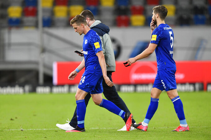 Schalke's Bastian Oczipka, left and Schalke's Matija Nastasic leave the field at the end of the German Bundesliga soccer match between Fortuna Duesseldorf and FC Schalke 04 in Duesseldorf, Germany, Wednesday, May 27, 2020. The German Bundesliga becomes the world's first major soccer league to resume after a two-month suspension because of the coronavirus pandemic. (AP Photo/Martin Meissner, Pool)