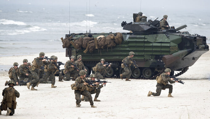 """FILE - In this June 4, 2018, file photo, U.S. Marines take a part in a military exercise in the Baltic Sea near the village of Nemirseta, about 340 kilometers (211 miles) northwest of Vilnius, the capital of the former Soviet republic of Lithuania. Ahead of a summit meeting between U.S. President Joe Biden and Russian President Vladimir Putin on June 16, 2021, Moscow has accused the European Union and NATO members that once were part of the Soviet Union or the Warsaw Pact of """"Russophobia,"""" casting them as key instigators of Western sanctions against Russia. (AP Photo/Mindaugas Kulbis, File)"""