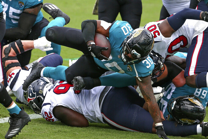 Jacksonville Jaguars running back James Robinson (30) dives over the Houston Texans defensive line for a 1-yard touchdown during the first half of an NFL football game, Sunday, Nov. 8, 2020, in Jacksonville, Fla. (AP Photo/Stephen B. Morton)