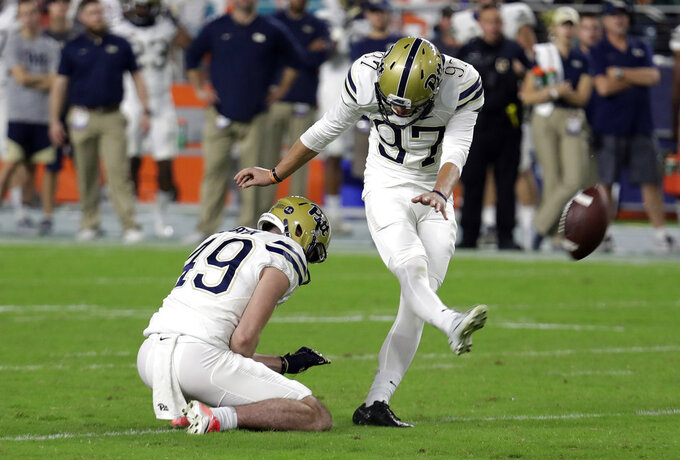 Pittsburgh placekicker Alex Kessman (97) kicks a field goal as Jake Scarton (49) holds during the second half of an NCAA college football game against Miami, Saturday, Nov. 24, 2018, in Miami Gardens, Fla. Miami won 24-3. (AP Photo/Lynne Sladky)
