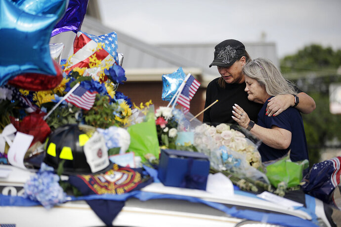 Anna Hok, left, and Terrie Dyer embrace and pray at a makeshift memorial for Tulsa Police Officers Craig Johnson and Aurash Zarkeshan at Mingo Valley Division in Tulsa Tuesday, June 30, 2020. The officers were shot early Monday morning during a traffic stop.  (Mike Simons/Tulsa World via AP)
