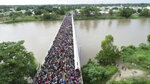 This frame grab from video provided by Televisa, shows migrants bound for the U.S.-Mexico border waiting on a bridge that stretches over the Suchiate River, connecting Guatemala and Mexico, in Tecun Uman, Guatemala, Friday, Oct. 19, 2018.  The gated entry into Mexico via the bridge has been closed. The U.S. president has made it clear to Mexico that he is monitoring its response. On Thursday he threatened to close the U.S. border if Mexico didn't stop the caravan. (Televisa via AP)