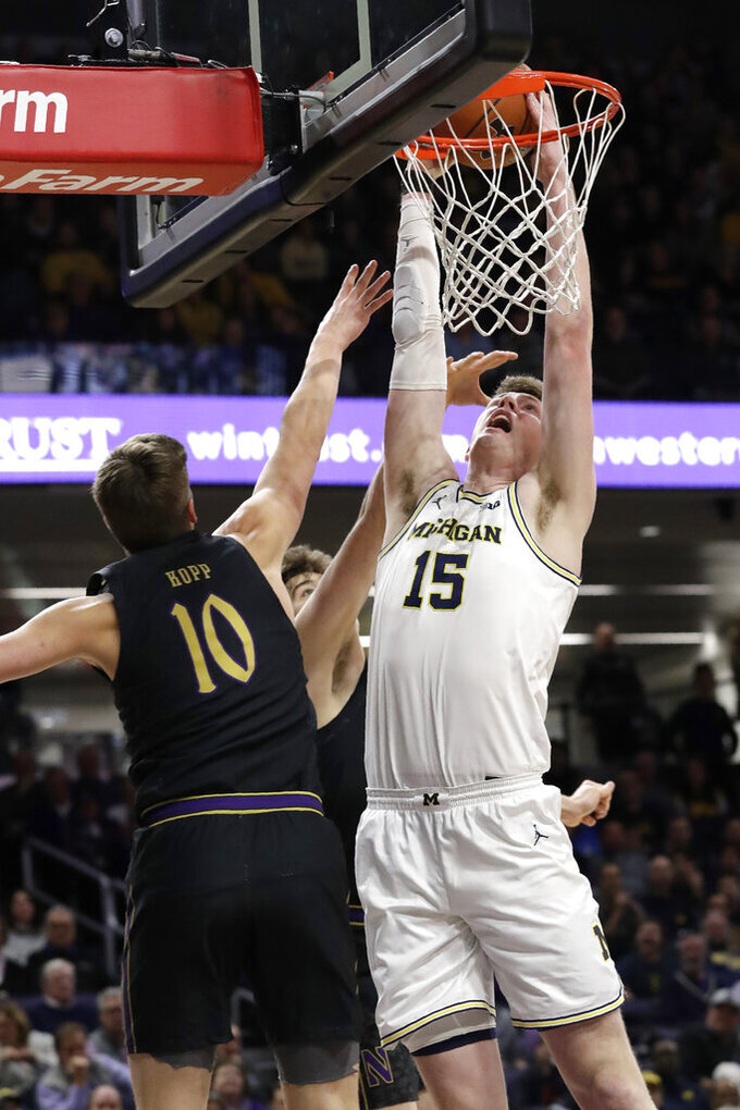 Michigan center Jon Teske, right, goes up for a shot against Northwestern forward Miller Kopp, left, and center Ryan Young during the first half of an NCAA college basketball game in Evanston, Ill., Wednesday, Feb. 12, 2020. (AP Photo/Nam Y. Huh)