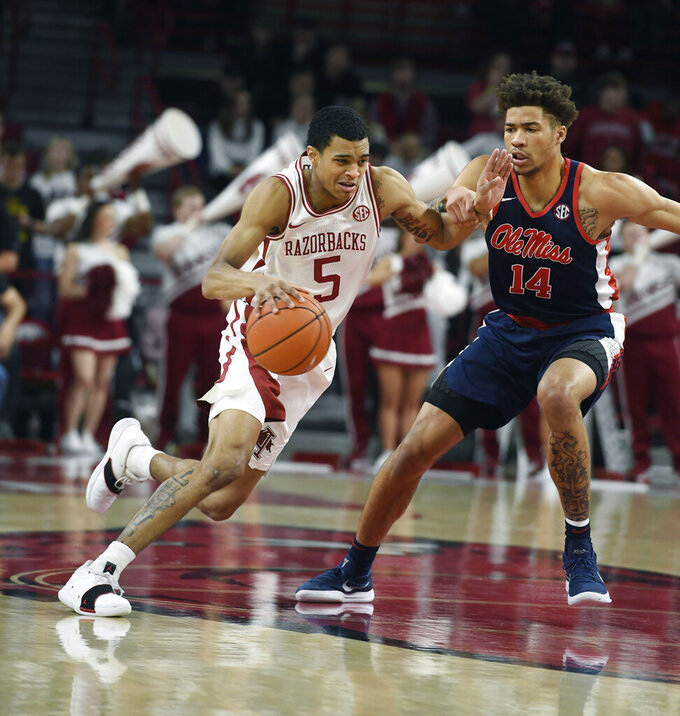 Arkansas guard Jalen Harris (5) tries to get past Mississippi defender KJ Buffen (14) during an NCAA college basketball game, Saturday, March 2, 2019 in Fayetteville, Ark. (AP Photo/Michael Woods)