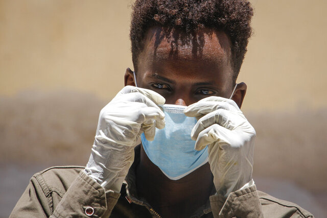 A Somali man wears a surgical mask and gloves on the street after after the government announced the closure of schools and universities and banned large gatherings, following the announcement on Monday of the country's first case of the new coronavirus, in the capital Mogadishu, Somalia Wednesday, March 18, 2020. For most people, the new coronavirus causes only mild or moderate symptoms such as fever and cough and the vast majority recover in 2-6 weeks but for some, especially older adults and people with existing health issues, the virus that causes COVID-19 can result in more severe illness, including pneumonia. (AP Photo/Farah Abdi Warsameh)